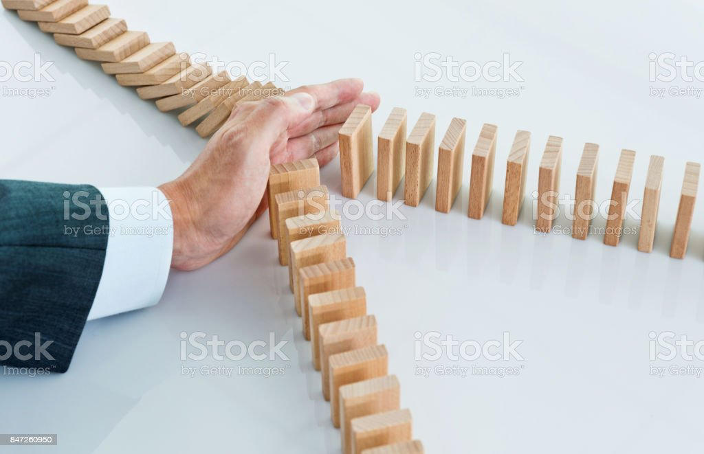 Businessman hand stopping falling blocks on table stock photo