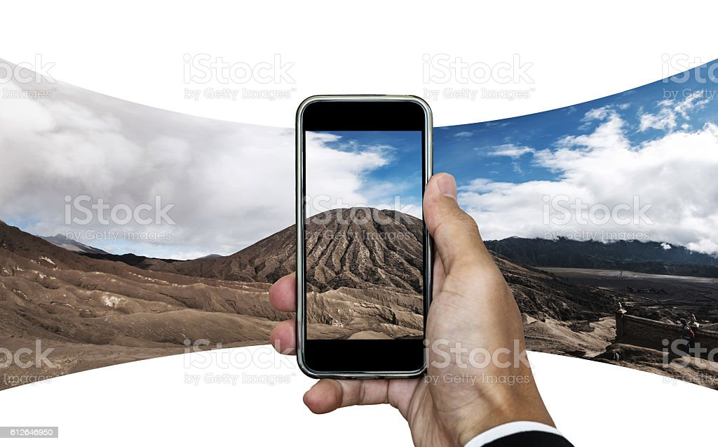 Businessman hand taking panorama photo of mountain landscape stock photo