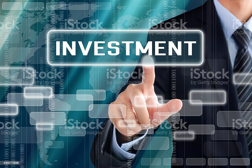 Businessman hand touching INVESTMENT sign on virtual screen stock photo