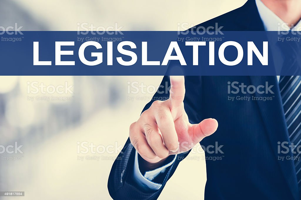 Businessman hand touching LEGISLATION sign on virtual screen stock photo