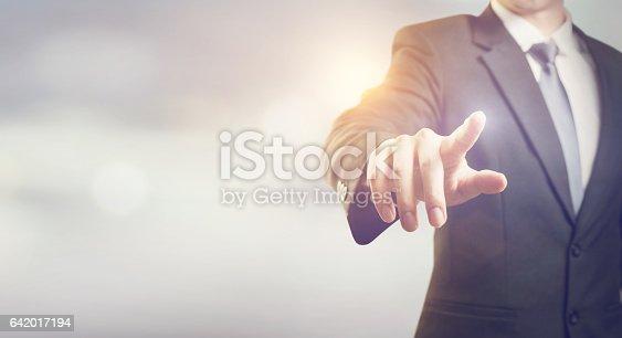 istock Businessman hand touching virtual screen 642017194
