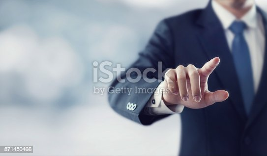 istock Businessman hand touching virtual screen 871450466
