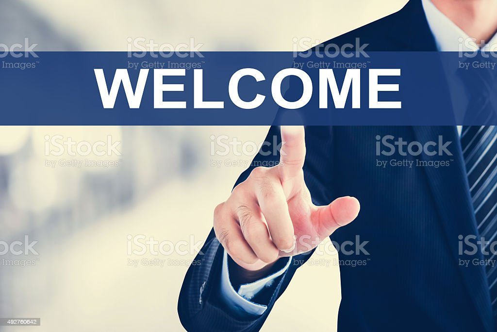 Businessman hand touching WELCOME sign on virtual screen stock photo