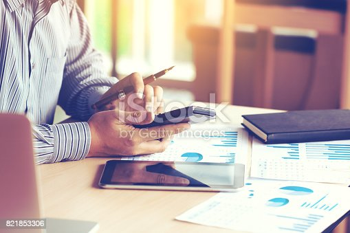istock Businessman hand typing button on calculator with calculating about expenditure for company in office and apply technology with laptop and tablet for searching data result. 821853306