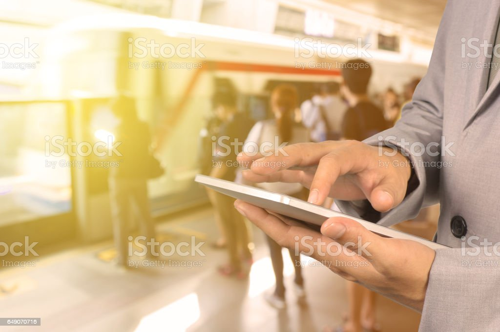 Businessman Hand use Wireless Tablet PC Device in Railway Station stock photo