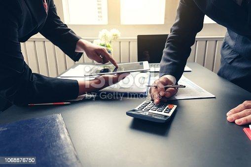 1068752548 istock photo Businessman hand using calculator at meeting. 1068876750