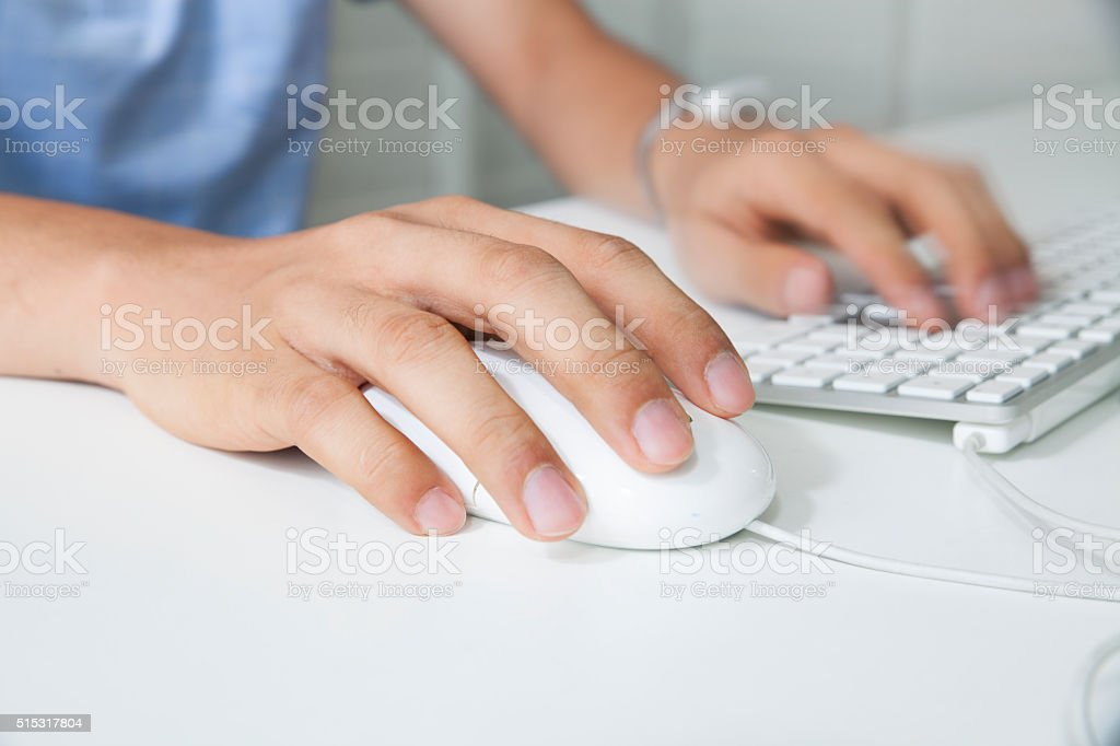 Businessman hand using computer mouse and keyboard stock photo
