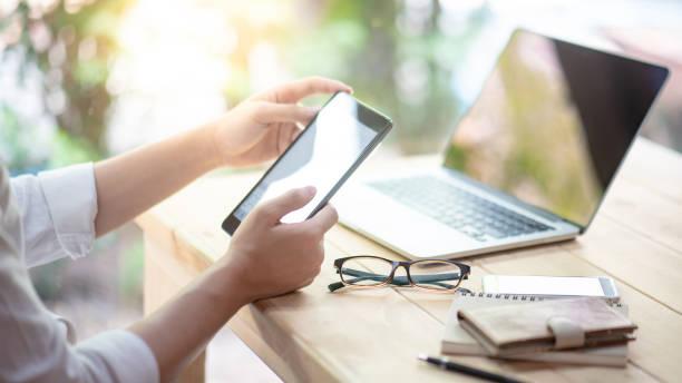 공동 작업 공간에서 노트북 컴퓨터와 스마트 폰과 작업 하는 디지털 태블릿을 사용 하 여 사업가 손. 현대 전자 장치를 갖춘 도시 라이프 스타일. 사물 인터넷 및 온라인 앱 컨셉 - 디지털 태블릿 사용하기 뉴스 사진 이미지