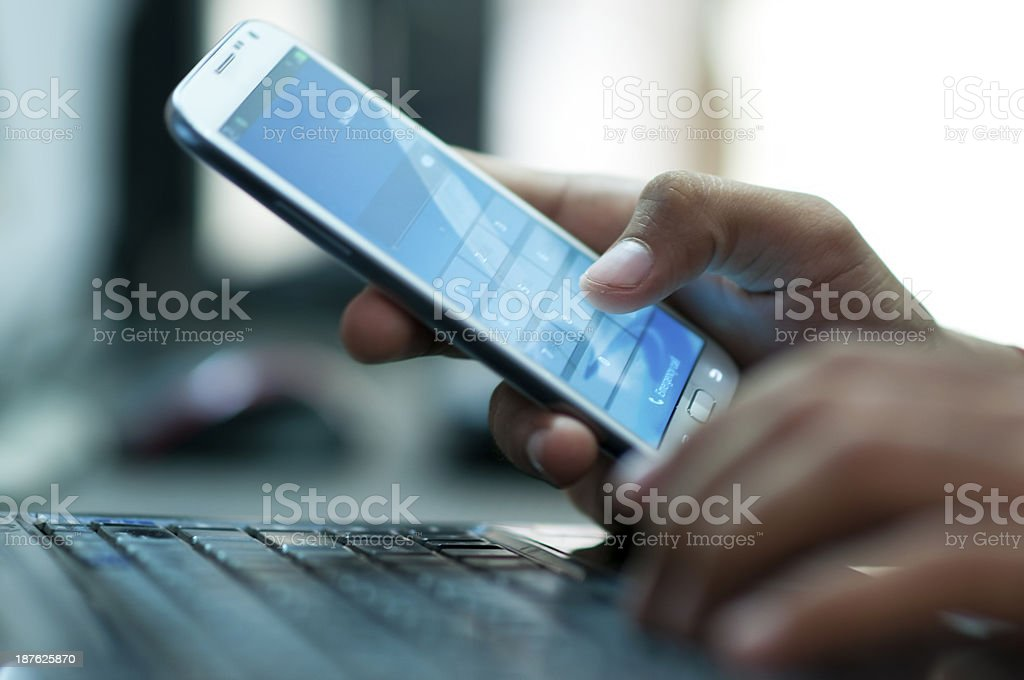 Businessman hand using laptop and mobile phone in office stock photo