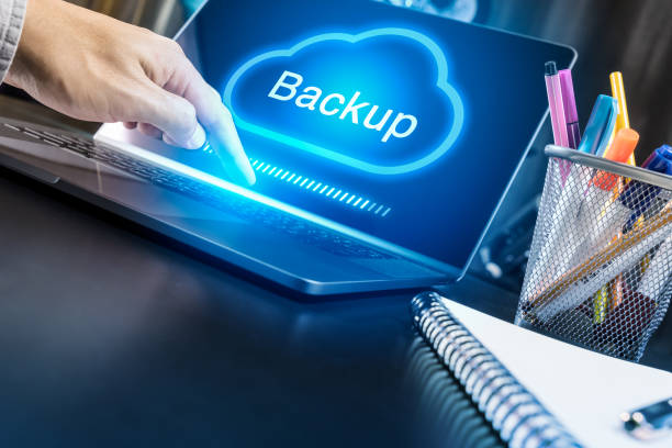 Businessman hand using modern laptop with Cloud Backup concept stock photo