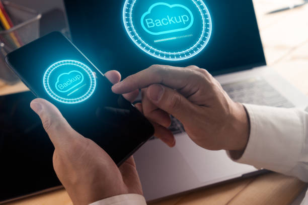 Businessman hand using smart phone and modern laptop computer with Cloud backup technology stock photo
