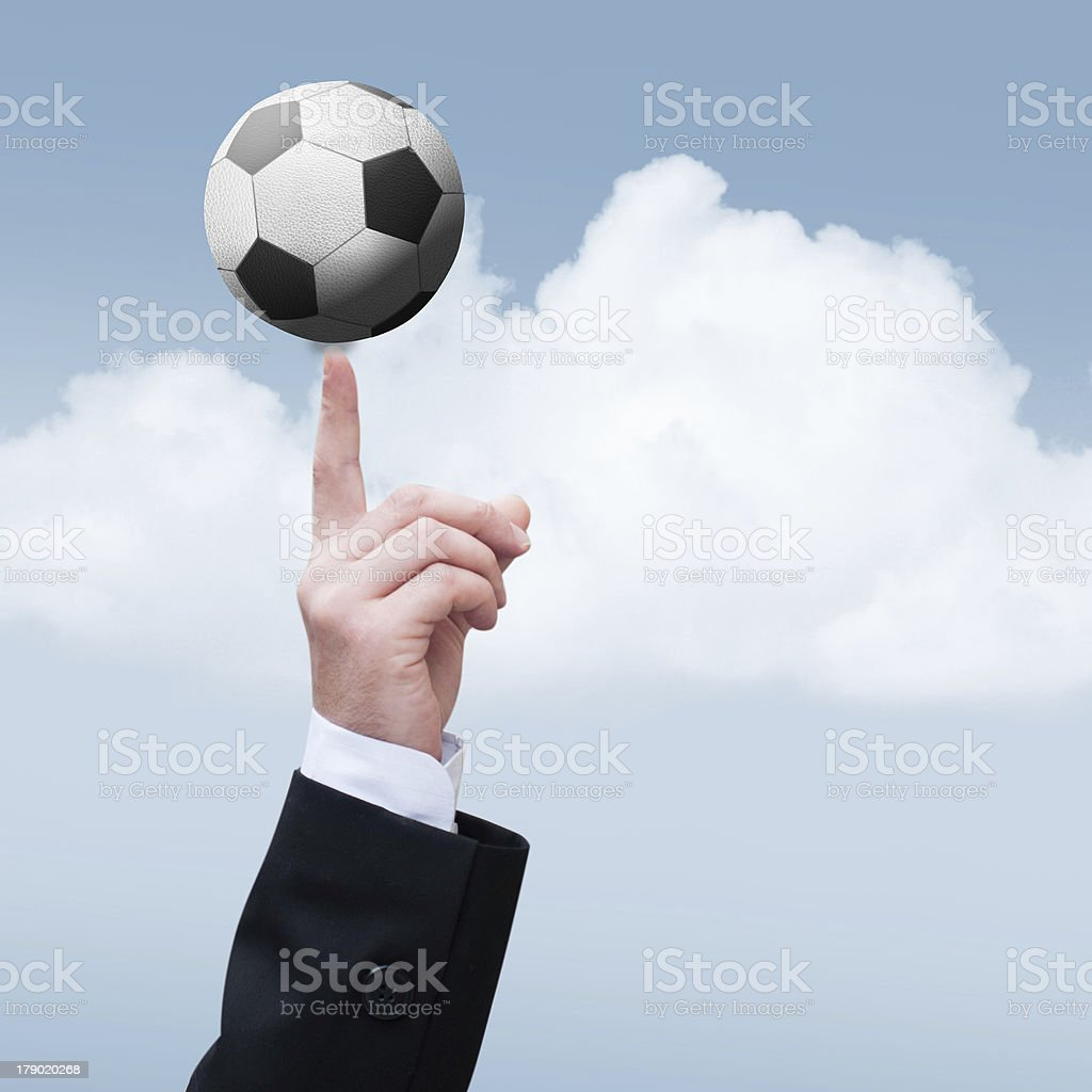 Businessman hand with the finger holding a small foot-ball royalty-free stock photo