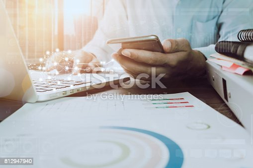 istock businessman hand working laptop on wooden desk in office in morning light. vintage effect 812947940