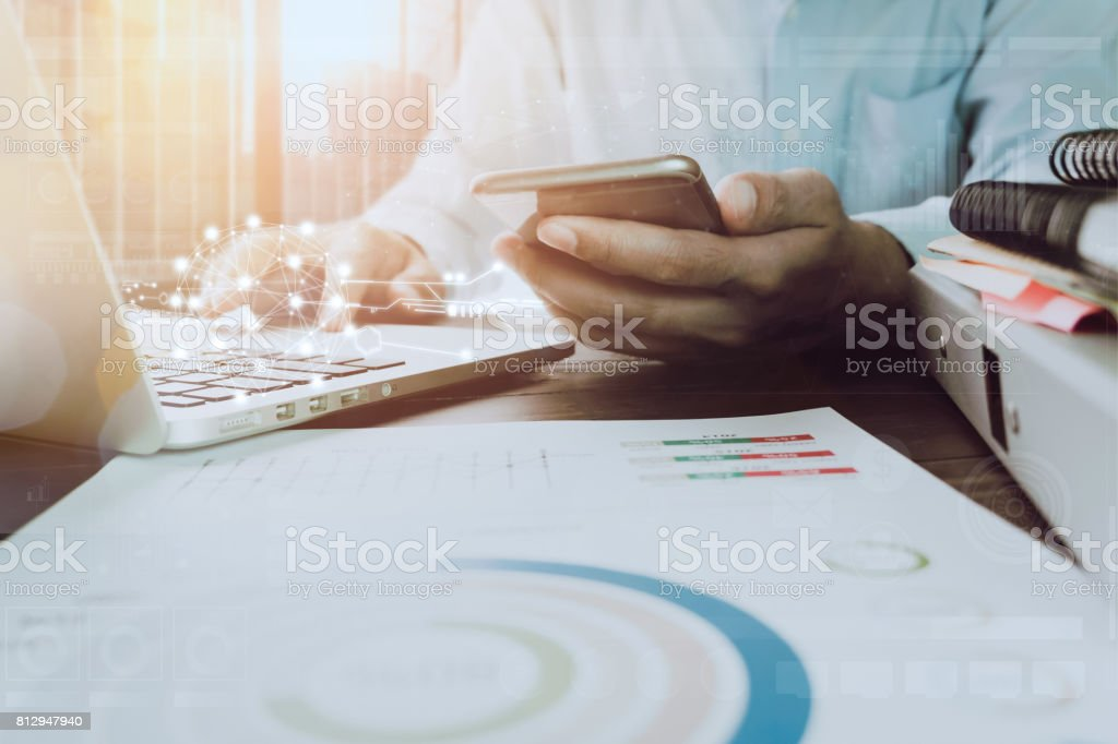 businessman hand working laptop on wooden desk in office in morning light. vintage effect stock photo