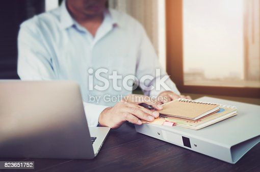 istock businessman hand working laptop on wooden desk in office in morning light. The concept of modern work with advanced technology. vintage effect 823651752