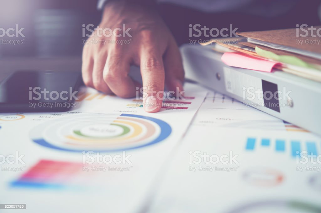 businessman hand working laptop on wooden desk in office in morning light. The concept of modern work with advanced technology. vintage effect stock photo