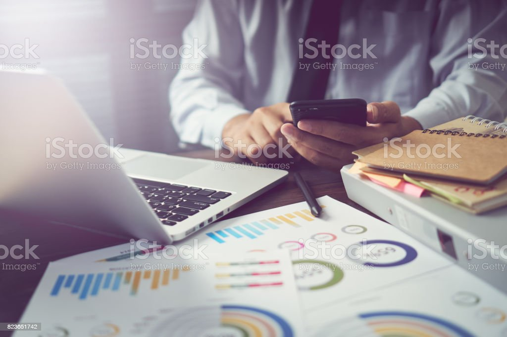 businessman hand working smart phone on wooden desk in office in morning light. The concept of modern work with advanced technology. vintage effect stock photo