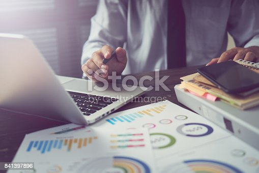 istock businessman hand working smart phone on wooden desk in office in morning light. The concept of modern work with advanced technology. vintage effect. 841397896