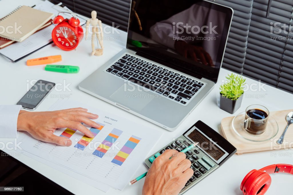Businessman hand working with financial data and calculator  on white desk - Royalty-free Adult Stock Photo