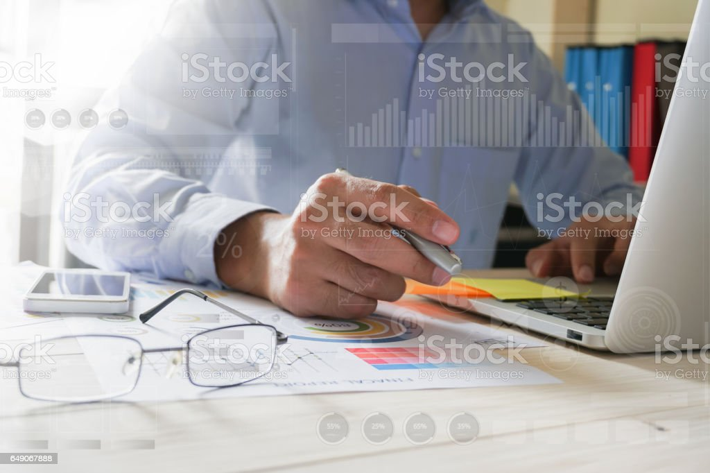 businessman hand working with laptop on wooden desk in office. can be used on an ad – zdjęcie