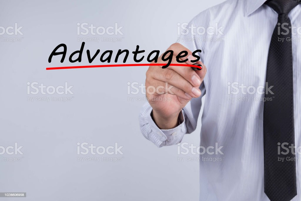 Businessman hand writing advantages with red marker on transparent wipe board, business concept. stock photo