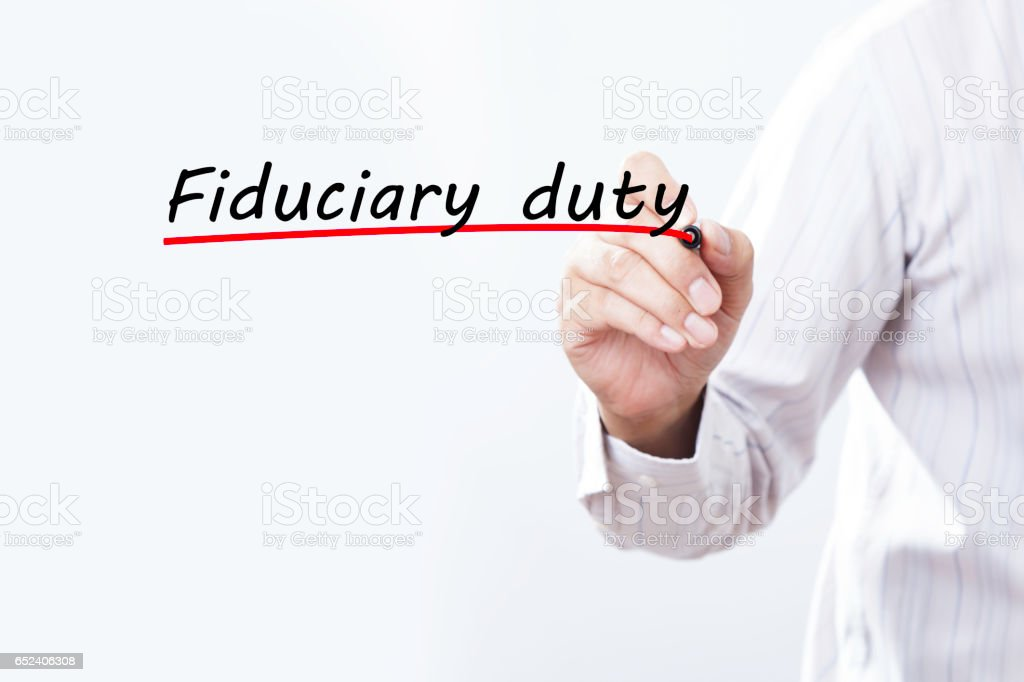 Businessman hand writing Fiduciary duty with red marker on transparent wipe board, business concept. stock photo