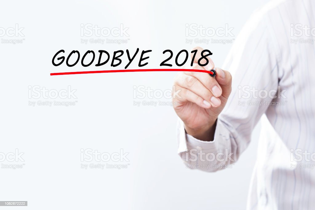 Businessman hand writing goodbye 2018 with red marker on transparent wipe board, business concept stock photo