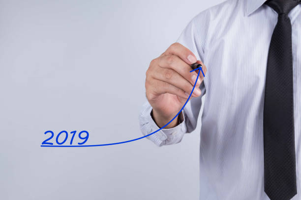 Businessman hand writing growth graph for year 2018. Business, finance, salary, crisis, and development concept. New year planing. stock photo