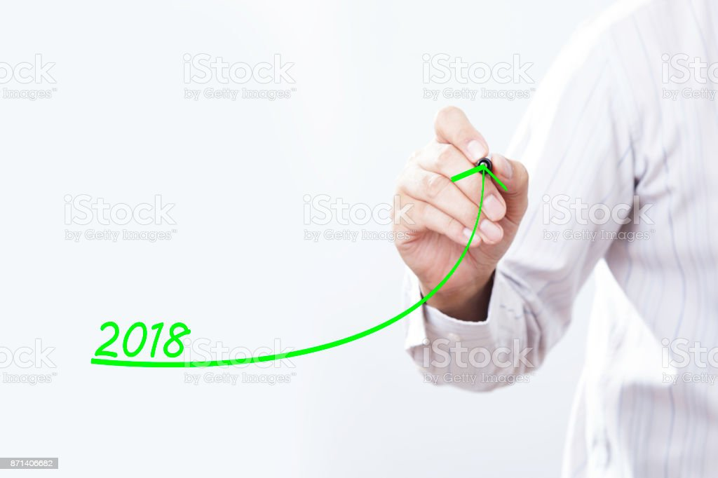 Businessman hand writing growth graph for year 2018 stock photo