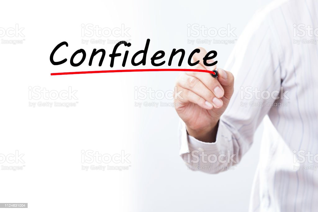 Businessman hand writing inscription 'Confidence' with marker, concept stock photo