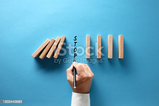 Businessman hand writing the word stop to prevent wooden dominos from collapsing on blue background.