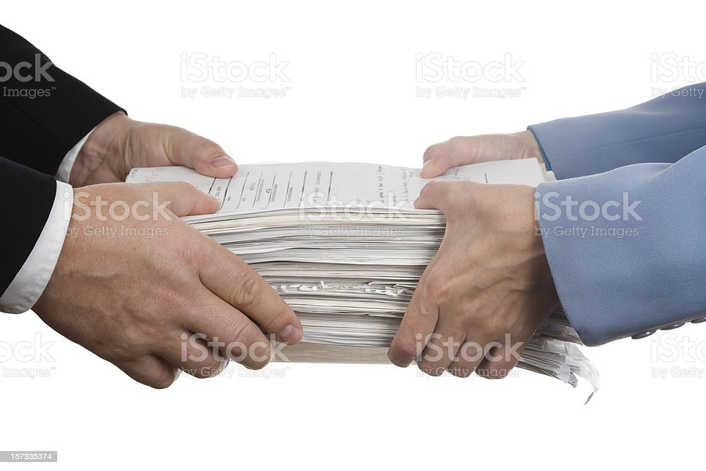 Businessman handing employee a large stack of excess papers royalty-free stock photo