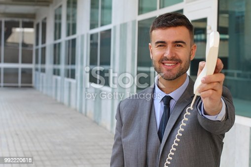 Businessman handing you a corded telephone.
