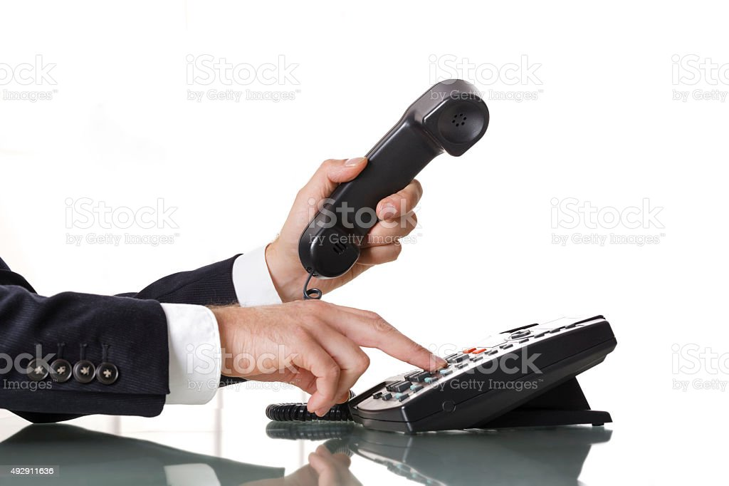 businessman hands dialing out on a black deskphone stock photo
