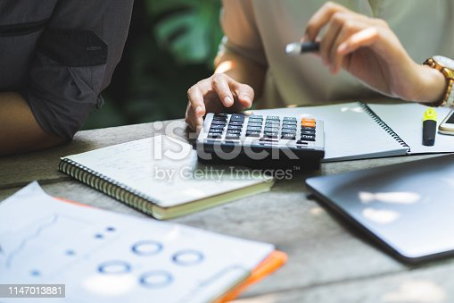 Businessman hands, he is pressing the calculator to calculate the amount