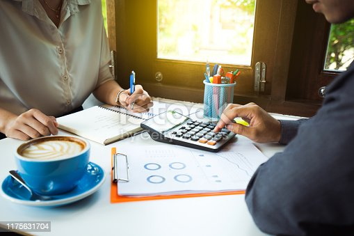 952991586istockphoto Businessman hands, he is pressing the calculator to calculate the amount 1175631704