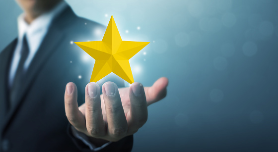 917079212 istock photo Businessman hands hold a five-star gold shape. The best excellent business services rating customer experience concept 1147251259