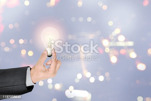 Businessman hands holding bright light bulb as a symbol of creative idea over blurred light background