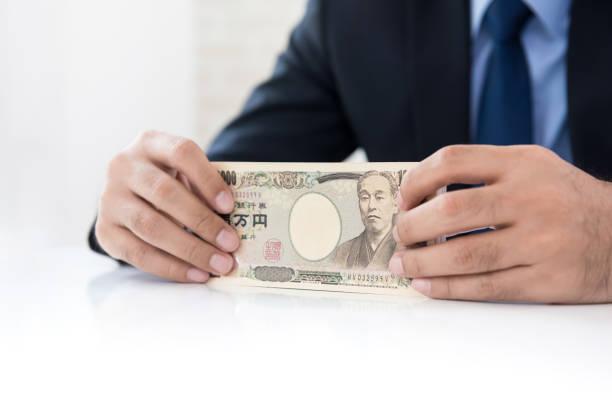 テーブルでお金を日本円の通貨を保持している実業家の手 ストックフォト