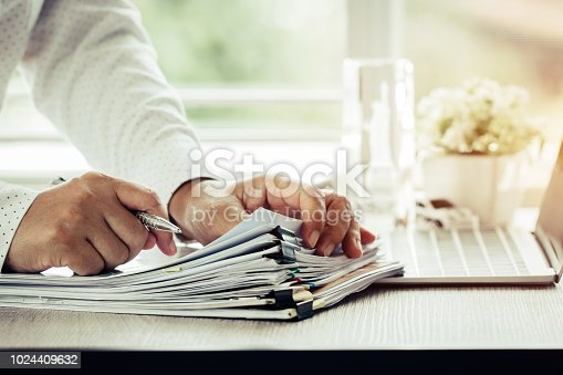 istock Businessman hands holding pen for working in Stacks of paper files searching information business report papers and piles of unfinished documents achieves on laptop computer desk in modern office 1024409632