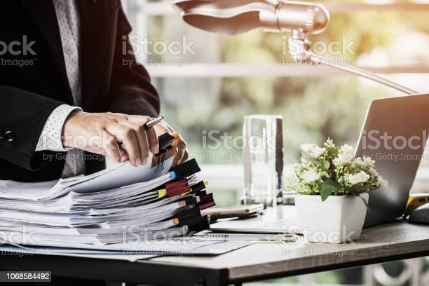 Businessman Hands Holding Pen For Working In Stacks Of Paper Files Searching Information Business Report Papers And Piles Of Unfinished Documents Achieves On Laptop Computer Desk In Modern Office Stock Photo - Download Image Now