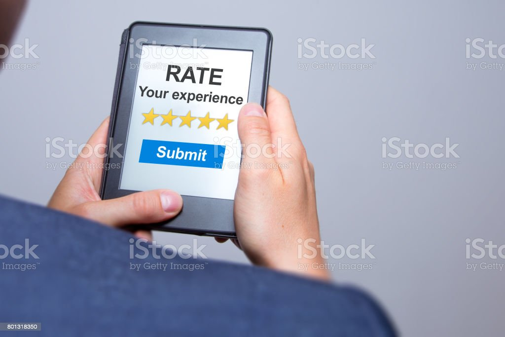 Businessman hands holding tablet with Rate your experience. Business concept. Stock photo stock photo