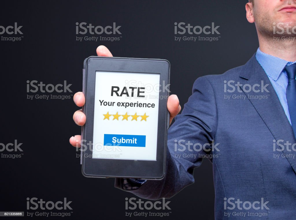 Businessman hands holding tablet with Rate your experience. Business concept. Isolated on black. Stock photo stock photo