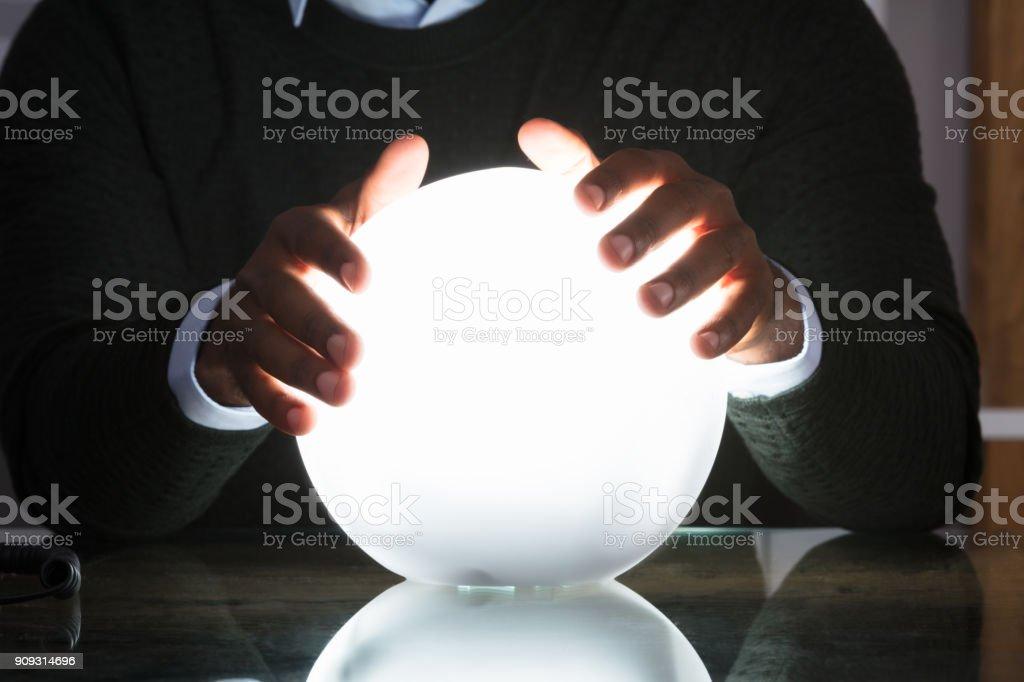 Mains d'homme d'affaires sur la boule de cristal - Photo