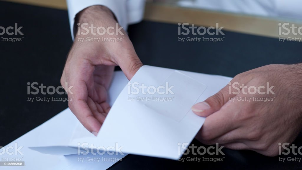 Businessman hands opening an envelope stock photo