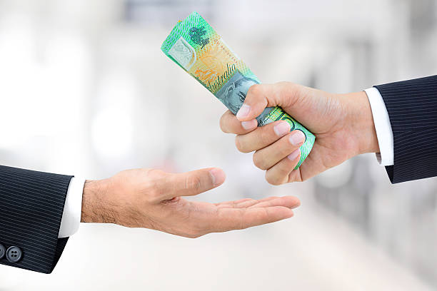 Businessman hands passing money, Australian dollar (AUD) banknotes stock photo