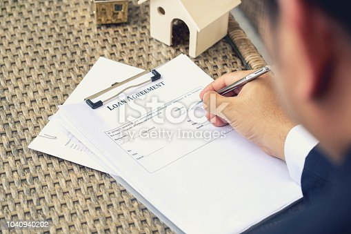 Businessman hands putting signature on document loan agreement, contract for buy new house.