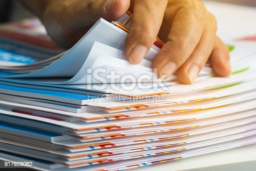 Businessman hands searching unfinished documents stacks of paper files on office desk for report papers, piles of sheet achieves with clips on table, Document is written, drawn,presented.