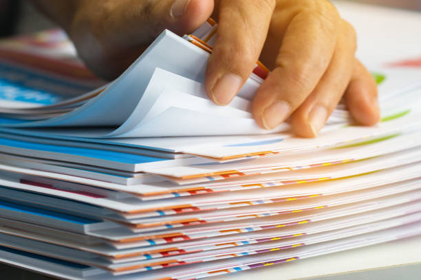 Businessman hands searching unfinished documents stacks of paper files on office desk for report papers, piles of sheet achieves with clips on table, Document is written, drawn,presented. stock photo