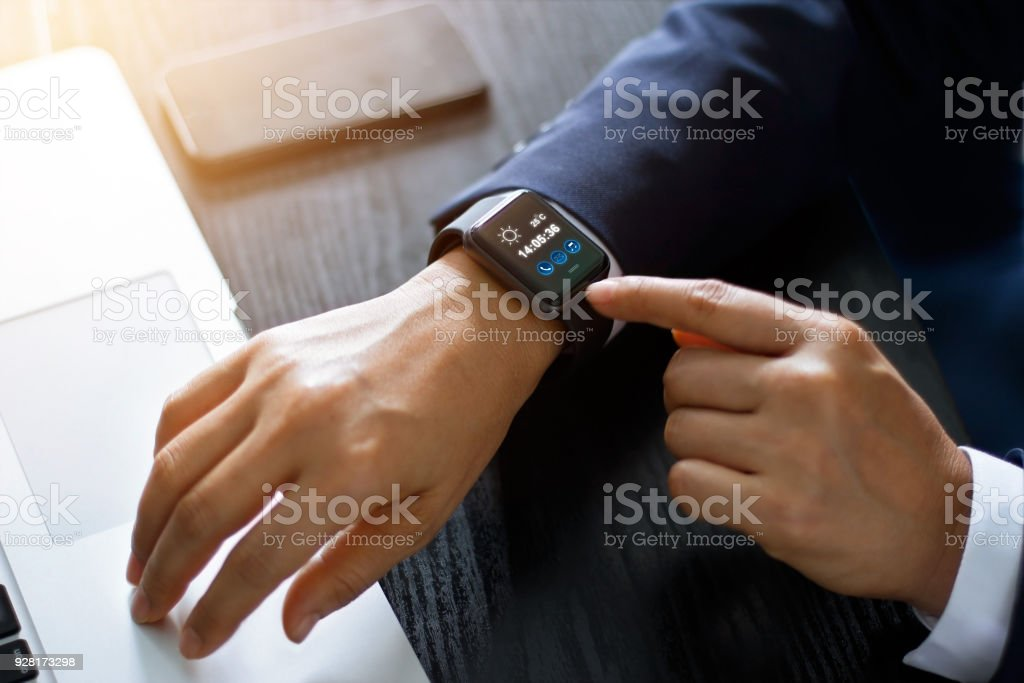 Businessman hands using smart watch app over laptop and smartphone on working desk, technology and communication concept. All on screen are design up. stock photo